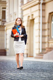 Portrait of happy smiling business woman with red folder in city Stock Photos
