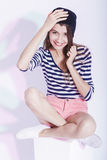 Portrait of  Happy Smiling Caucasian Brunette in Hat and Striped Shirt Posing in Studio Against White. Royalty Free Stock Image