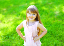 Portrait of happy smiling child little girl on the grass Stock Photos