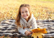 Portrait of happy smiling child lying on plaid with leafs Royalty Free Stock Image