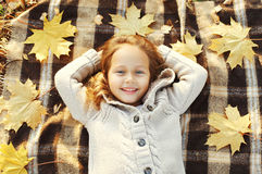 Portrait happy smiling child lying on plaid with yellow maple le Royalty Free Stock Image