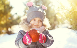 Portrait happy smiling child with red christmas ball in winter Royalty Free Stock Images