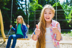 Portrait of happy and smiling child show thumb up at park. On the background other girl riding a swing Stock Images