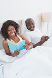 Portrait of a happy smiling couple reading in bed together Royalty Free Stock Images