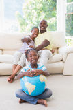 Portrait of a happy smiling couple sitting on couch and daughter taking a globe royalty free stock image