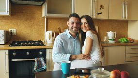 Portrait of happy smiling couple sittting in the kitchen early morning at home Royalty Free Stock Image