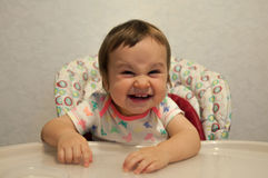 Portrait of happy smiling cunning baby girl in high chair. Concept of baby feeding, hungry child, good appetite, food. Portrait of happy smiling cunning baby Stock Photo