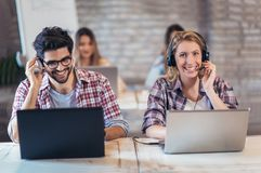 Portrait of happy smiling customer support phone operator at wor. Kplace Royalty Free Stock Image