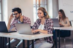 Portrait of happy smiling customer support phone operator at wor. Kplace Stock Photos