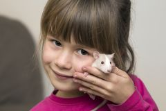 Portrait of happy smiling cute child girl with white pet mouse hamster on light copy space background. Keeping pets at home, care. And love to animals concept royalty free stock photo