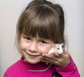 Portrait of happy smiling cute child girl with white pet mouse hamster on light copy space background. Keeping pets at home, care. And love to animals concept royalty free stock photos