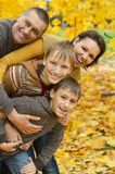 Smiling family in autumn forest Royalty Free Stock Photos