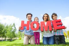 Happy family and their house. Portrait of happy smiling family and their children holding home letters near their house Royalty Free Stock Photos