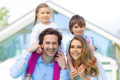 Happy family and their house. Portrait of happy smiling family and their children near their house Stock Photography