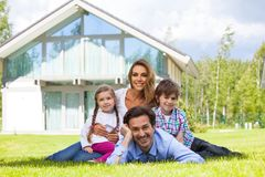 Happy family and their house. Portrait of happy smiling family and their children near their house Royalty Free Stock Photos