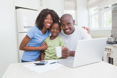 Portrait of a happy smiling family using computer. Portrait of happy smiling family using computer in the kitchen royalty free stock photos