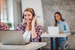 Portrait of happy smiling female customer support phone operator. At workplace Stock Photos