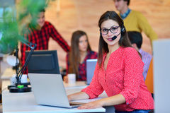 Portrait of happy smiling female customer support phone operator at workplace. Royalty Free Stock Image