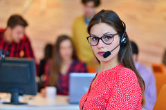Portrait of happy smiling female customer support phone operator at workplace. Stock Photos