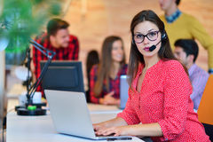 Portrait of happy smiling female customer support phone operator at workplace. Stock Photography