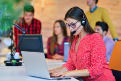 Portrait of happy smiling female customer support phone operator at workplace. Stock Images