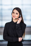 Portrait of happy smiling female customer support phone operator at workplace background Stock Image