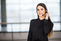 Portrait of happy smiling female customer support phone operator at workplace background Royalty Free Stock Photos