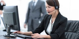 Smiling female customer support phone operator at workplace. Portrait of happy smiling female customer support phone operator at workplace Royalty Free Stock Images