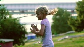 Portrait of happy smiling girl in city park jumping, turning around and clapping. She smiles in delight and enjoys the stock footage