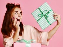 Happy young woman with gifts over pink background. royalty free stock photos