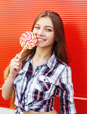Portrait happy smiling girl with sweet caramel lollipop having fun over red Stock Images