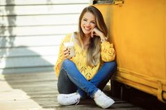 Happy smiling woman is wearing yellow sweater drinking coffee near old retro bus. Portrait of happy smiling girl is wearing yellow knitted sweater and jeans is Stock Images