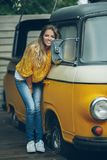 Happy smiling girl is wearing yellow sweater near old retro bus, autumn concept Royalty Free Stock Photo