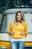 Happy smiling girl is wearing yellow sweater near old retro bus Royalty Free Stock Image