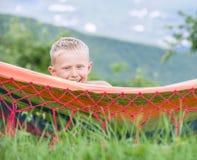 Portrait happy smiling little boy lying in hammock Royalty Free Stock Images