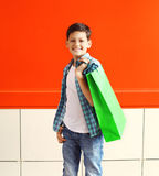 Portrait happy smiling little boy teenager with shopping bag in city. Over red background Stock Photo