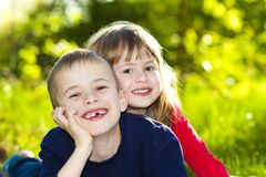 Portrait of happy smiling little children boy and girl on sunny. Summer grass meadow royalty free stock photo