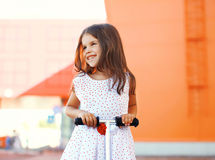 Portrait of happy smiling little girl on the scooter having fun Royalty Free Stock Photos
