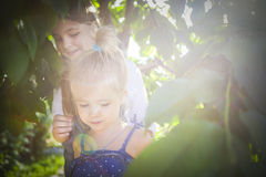 Portrait of happy smiling little sisters in sunny garden Royalty Free Stock Photos