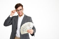 Portrait of happy smiling man in eyeglasses and a jacket. Showing bunch of money banknotes while standing and looking away at copy space isolated over white Stock Photos