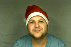 Portrait of a happy smiling man in a Suite and red cap like Santa keeps the gifts to a Young Santa Claus in a real house or car fo stock photo