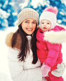 Portrait happy smiling mother and child in snowy winter. Day Royalty Free Stock Photography