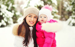 Portrait happy smiling mother and child in snowy winter Royalty Free Stock Image