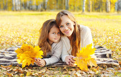Portrait happy smiling mother and child together with maple leafs Stock Photo