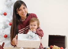 Portrait of happy smiling mother and her baby near Christmas tre Royalty Free Stock Photos