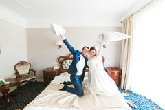 Portrait of happy smiling newlywed couple fighting with pillows on bed in hotel room Royalty Free Stock Photo