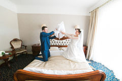 Portrait of happy smiling newlywed couple fighting with pillows on bed in hotel room Royalty Free Stock Image