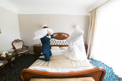 Portrait of happy smiling newlywed couple fighting with pillows on bed in hotel room Royalty Free Stock Photography