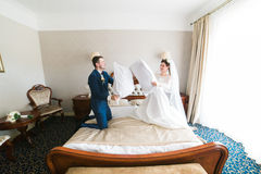 Portrait of happy smiling newlywed couple fighting with pillows on bed in hotel room Stock Image