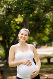 Portrait of happy and smiling pregnant woman in park Royalty Free Stock Images